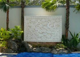 Batu alam ukir (batu candi) berwarna putih dengan motif bunga dan daun lotus. Batu ukir diletakkan di taman belakang.