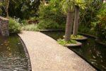 Jalur pejalan kaki menggunakan koral sikat tanpa motif berwarna terang di atas kolam.