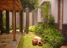 Pergola di atas carport rumah dengan material kayu.